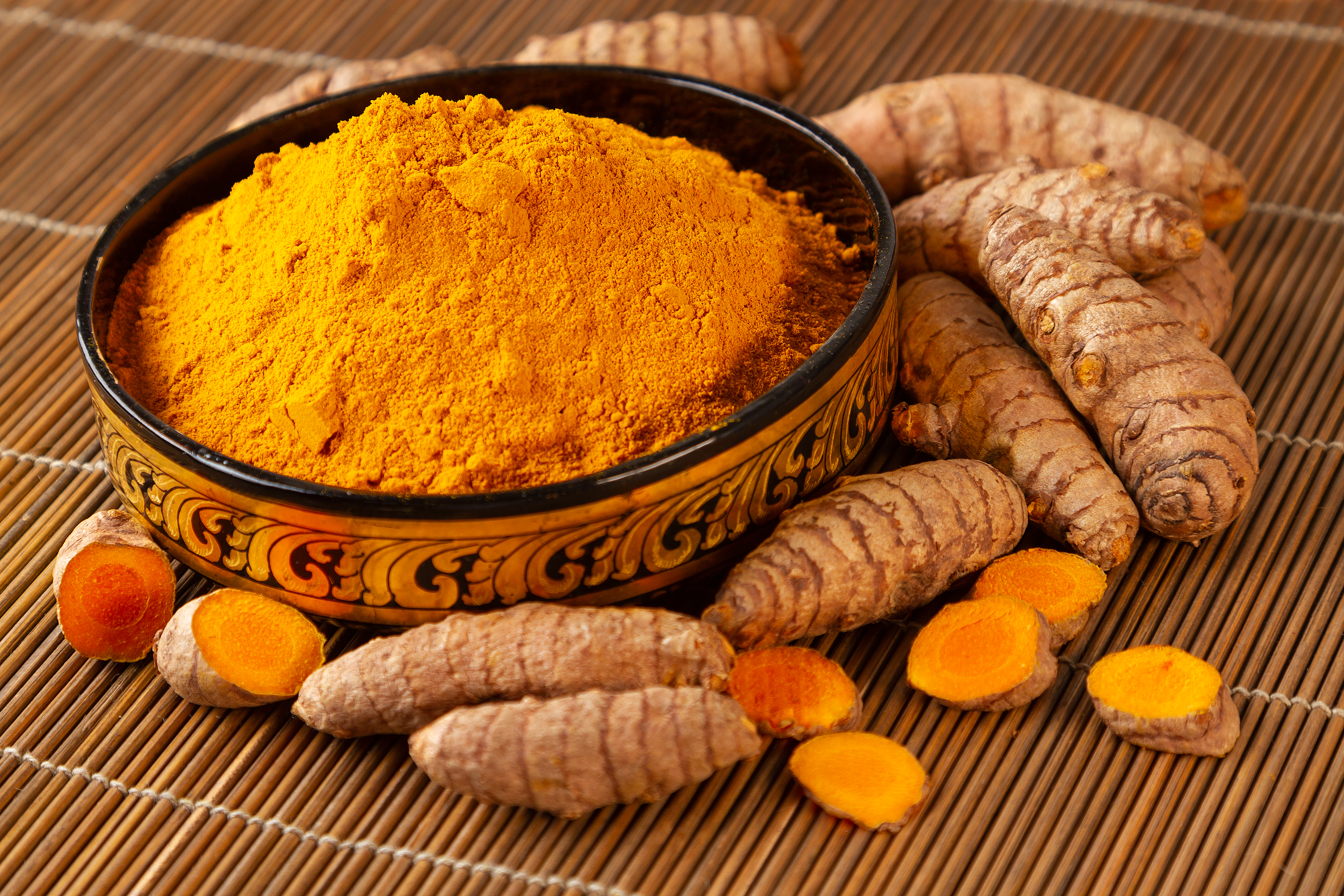 Turmeric powder and fresh roots in asian bowl closeup. Selective focus on turmeric powder