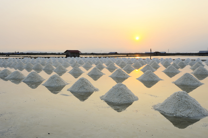 Sunset in a row Heap of sea salt prepared for harvest