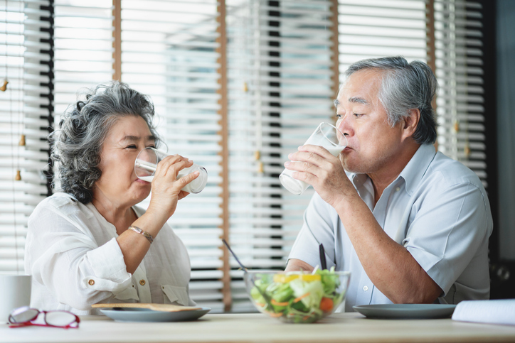 Smiling Asian senior man and woman drinking glasses of milk at home