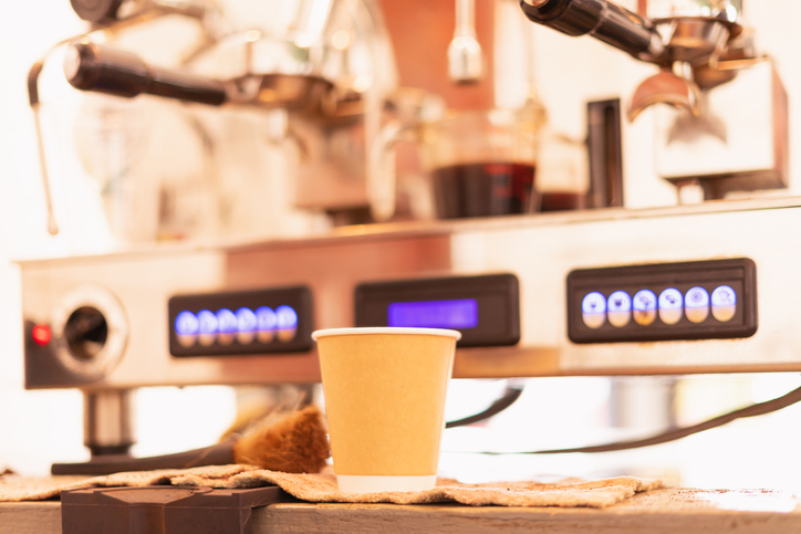 Grinder machine makes black coffee and flows it into takeaway coffee cup at coffee bar.