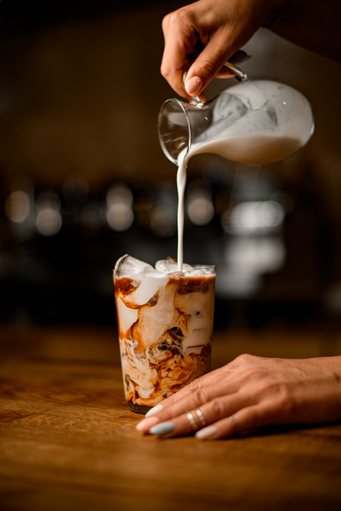 view of transparent glass with mixed coffee and milk and ice cubes. Woman's hand pours milk from jug into it